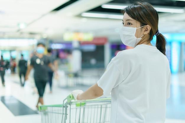 Mulher se protege de infecções com a máscara cirúrgica e luvas, com carrinho de compras para fazer compras no supermercado após pandemia de coronavírus.