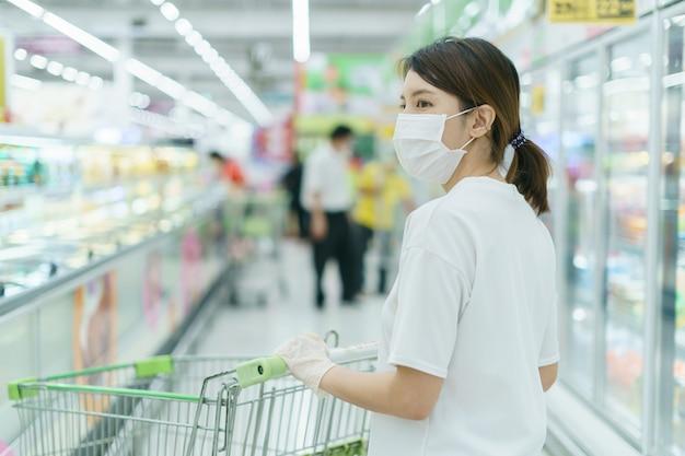 Mulher se protege de infecções com a máscara cirúrgica e luvas, com carrinho de compras para fazer compras no supermercado após uma pandemia de coronavírus.