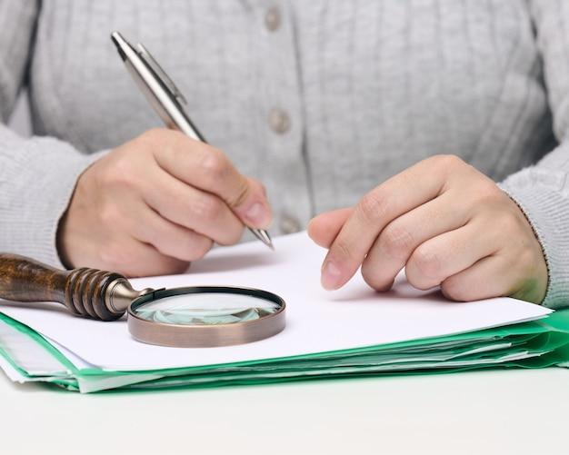 Mulher se senta a uma mesa branca e segura uma caneta de metal sobre uma pilha de papéis, na outra mão uma lupa. encontrando erros, analisando o orçamento