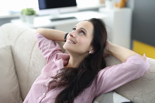 Mulher se senta no sofá com os braços cruzados atrás da cabeça e olha para cima com ar sonhador.