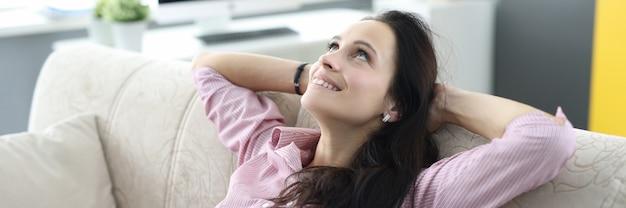 Mulher se senta no sofá e ergue os olhos com ar sonhador.