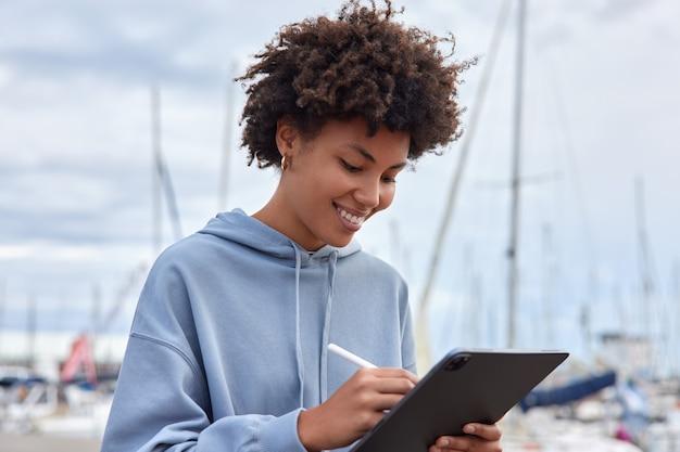 Mulher se sente feliz desenha esboços com caneta em tablet vestida com capuz poses porto marítimo ao ar livre faz desenhos para projeto futuro