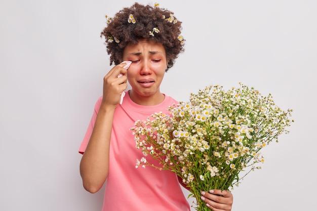 Mulher se sente mal por ser alérgica a flores silvestres segura buquê de camomila esfrega olhos vermelhos com lenço sofre de alergia sazonal isolada sobre o branco
