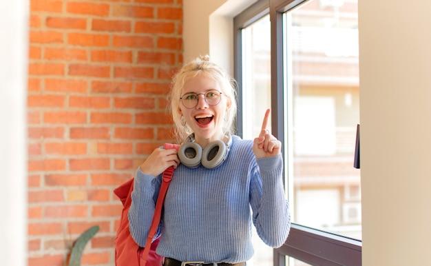 Mulher se sentindo como um gênio feliz e animado depois de realizar uma ideia, levantando o dedo alegremente, eureka!