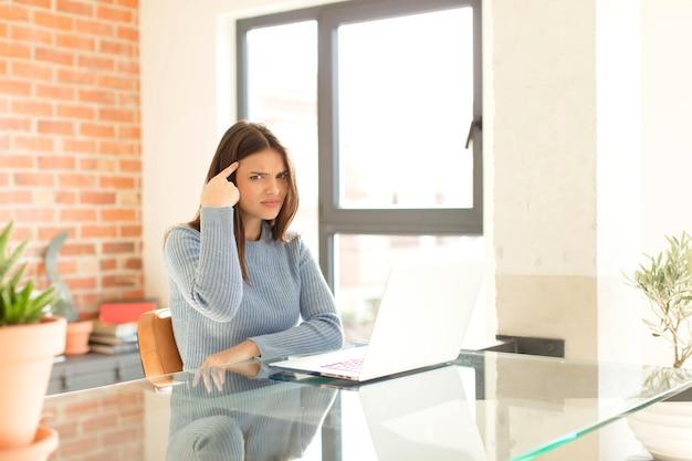 Mulher se sentindo confusa e perplexa, mostrando que você é louco, louco ou maluco