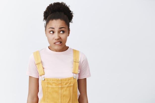 Mulher se sentindo culpada, querendo pedir desculpas. retrato de uma linda garota afro-americana nervosa e preocupada de macacão amarelo, mordendo o lábio e olhando ansiosamente para a direita, em pé sobre uma parede cinza