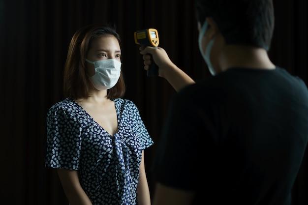 Mulher se sentindo doente e vestindo máscara protetora verificada pelo homem com máscara médica
