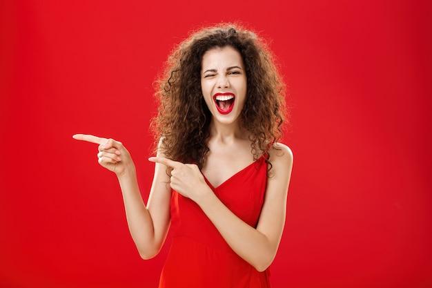 Mulher se sentindo incrível na grande festa do amigo apontando para a entrada. mulher elegante e despreocupada de cabelos cacheados em um vestido de noite vermelho, se divertindo perto da piscina, piscando, sorrindo alegremente e apontando para a esquerda.