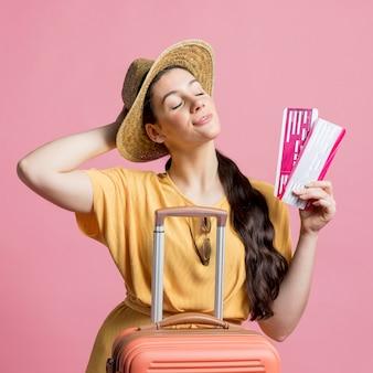 Mulher se sentindo relaxado, segurando bilhetes de avião