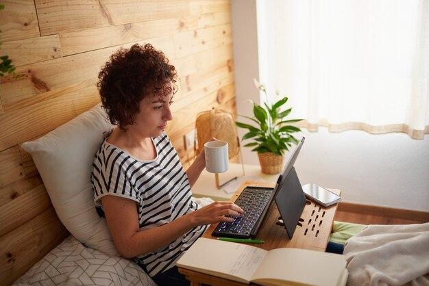 Mulher se teletransportando da cama, segurando uma xícara de café e digitando em seu tablet digital