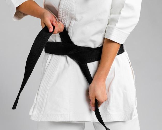Mulher se vestindo de uniforme e colocando o cinto