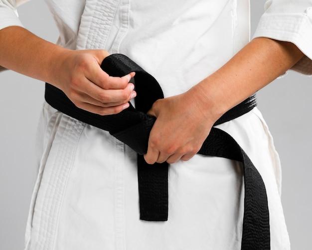 Mulher se vestindo de uniforme e faixa preta