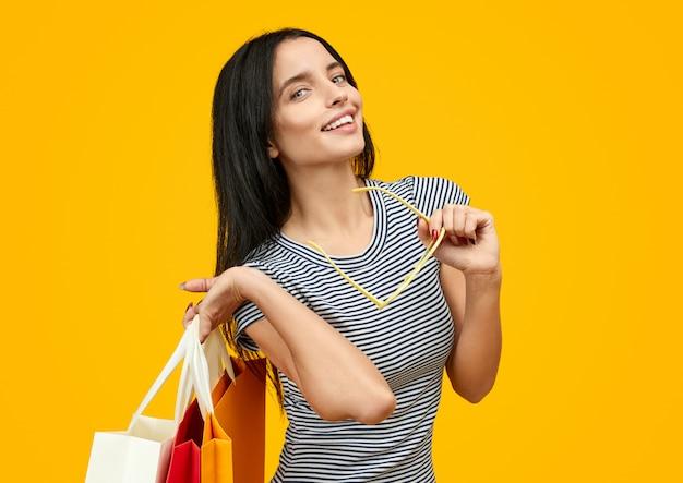 Mulher sedutora com sacos de papel olhando para a câmera