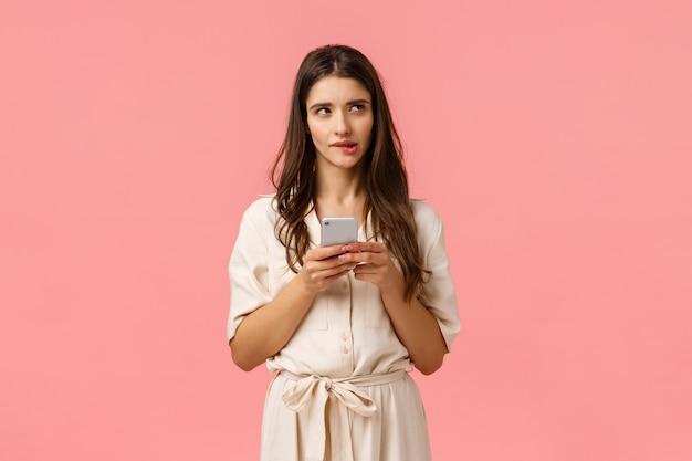 Mulher sedutora curiosa e sonhadora shoppaholic pensando que ordem melhor, mordendo o lábio olhando para imagens, segurando o telefone, não tenho certeza enviando mensagem arriscada, em pé parede rosa pensativo