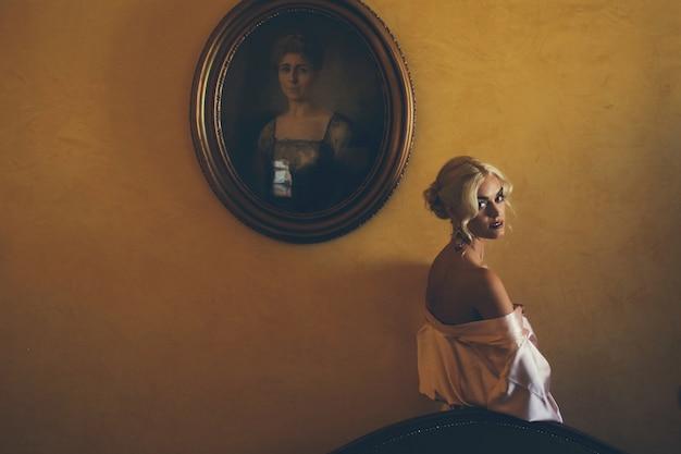 Mulher sedutora e loira olha os ombros de bronze enquanto ela