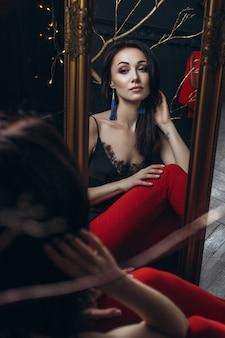 Mulher sedutora em terno vermelho senta-se diante de um espelho
