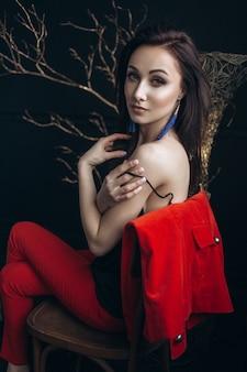 Mulher sedutora em traje vermelho senta-se diante de uma árvore brilhante
