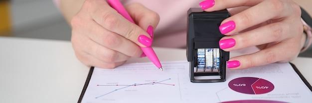 Mulher segura a caneta e coloca um carimbo em documentos com gráficos de negócios. carimbo de data em documentos