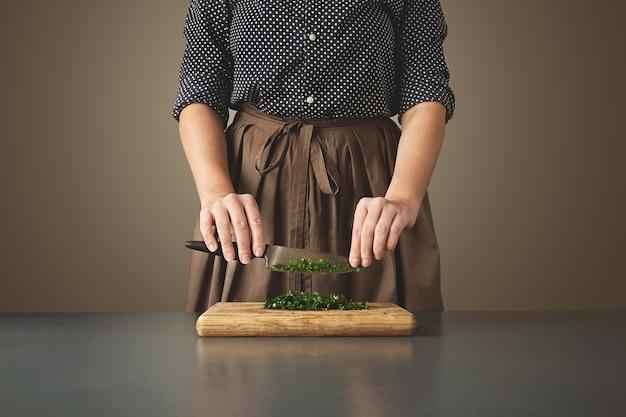 Mulher segura a faca acima da salsa verde picada na placa de madeira na mesa azul envelhecida.