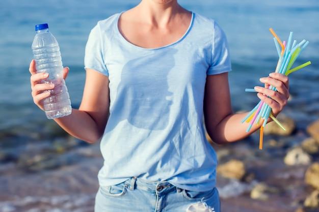 Mulher segura a garrafa de plástico e canudos nas mãos na praia. bata o conceito de poluição de plástico.
