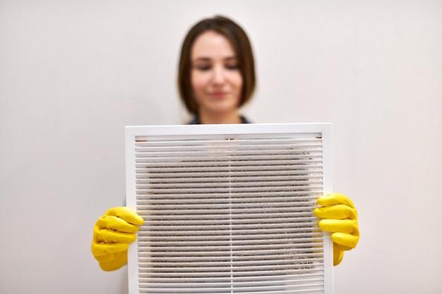 Mulher segura a grade de ventilação com filtro de poeira para limpá-la. plástico branco extremamente sujo e empoeirado, prejudicial à saúde
