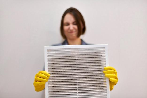 Mulher segura a grade de ventilação com filtro de poeira para limpá-la. plástico branco sujo e empoeirado, prejudicial à saúde. faxineira com expressão disfarçada, desfocada, com luvas de proteção de borracha e uniforme