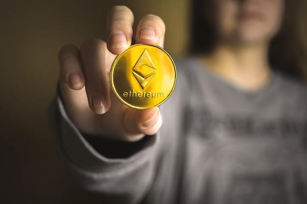 Mulher segura a moeda ethereum na mão, close-up da moeda cripto, troca de criptomoedas e foto de plano de fundo do conceito de investimento