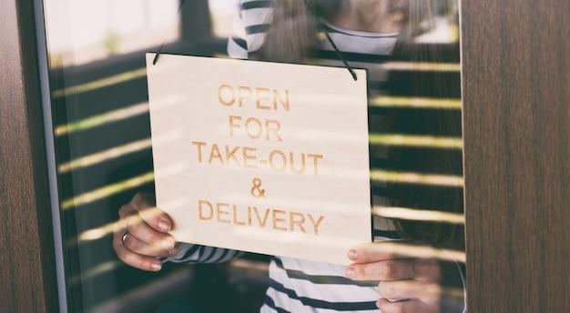Mulher segura a placa de madeira com o texto: aberto para entrega e entrega