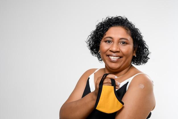 Mulher segura a proteção facial e mostra o adesivo da vacina no braço, mostrando confiança