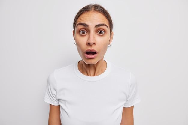 Mulher segura a respiração, não consegue acreditar que seus olhos mantêm a boca bem aberta vestida de merda casual em branco