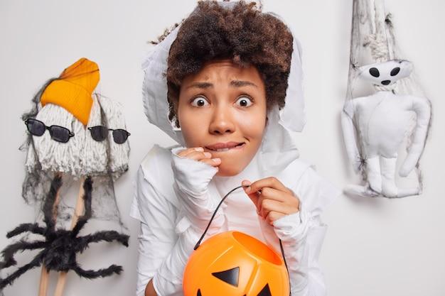 Mulher segura abóbora entalhada de criaturas assustadoras ao redor de lábios de mordidas vestidos com cotume fantasma isolado no branco