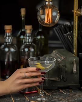 Mulher segura álcool beber guarnecido com casca de limão no copo de martini