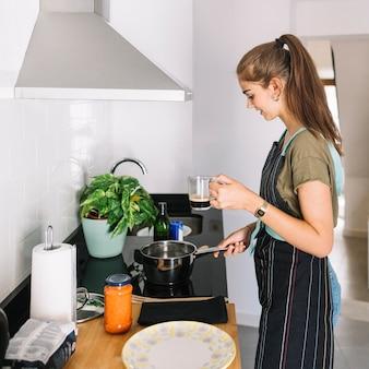 Mulher segura, assalte café, preparando alimento, cozinha