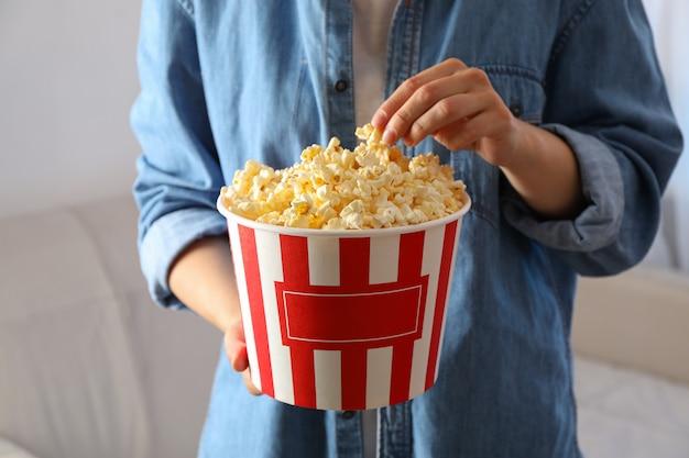 Mulher segura balde com pipoca. comida para assistir filmes