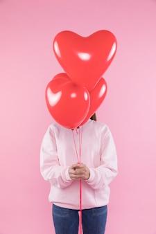 Mulher segura, balões vermelhos