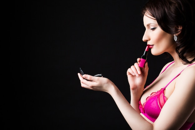Mulher segura batom rosa isolado em um fundo preto.