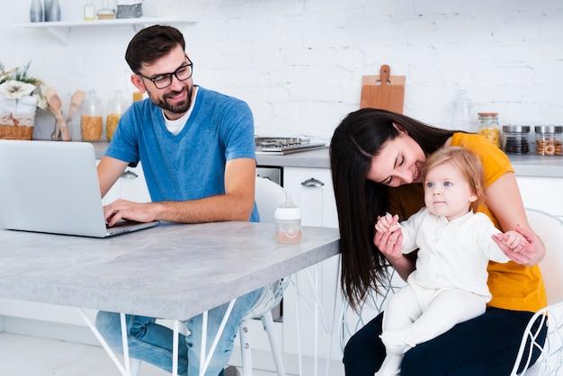 Mulher segura bebê, com, homem trabalha