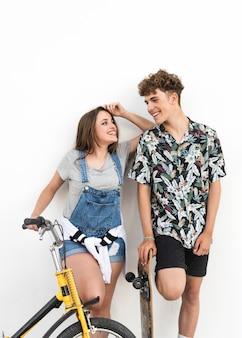 Mulher segura, bicicleta homem, segurando, skateboard, olhando um ao outro
