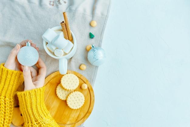 Mulher segura, bola natal, para, decoração, com, marshmallow chocolate, canela, biscoitos