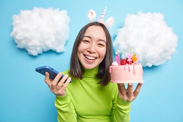 Mulher segura bolo de aniversário e dispositivo de smartphone sorri com os dentes contente por aceitar os parabéns por suas poses de 26º aniversário no azul