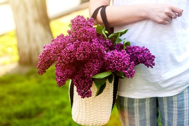 Mulher segura, bolsa palha, com, vívido, grupo, de, lilás, flores