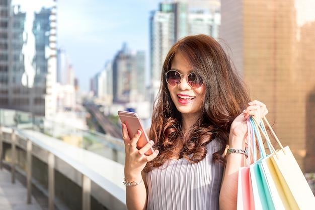 Mulher segura, bolsas para compras, e, esperto, telefone, em, mão, com, skyline, fundo