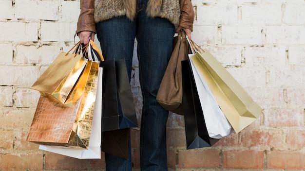 Mulher segura, bolsas para compras, perto, parede
