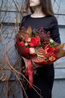 Mulher segura buquê de outono chique em cores vermelhas em estilo vintage ao ar livre