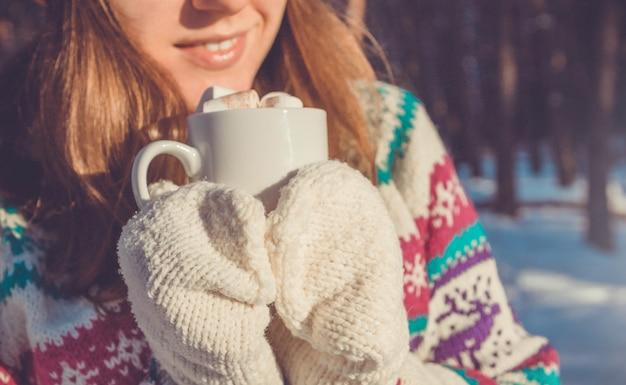 Mulher segura café com marshmallow na floresta de inverno