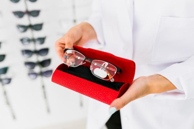 Mulher segura, caixa vermelha, e, óculos