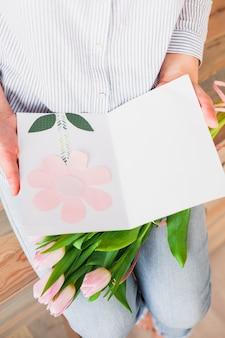 Mulher segura, cartão cumprimento, e, cor-de-rosa, flores