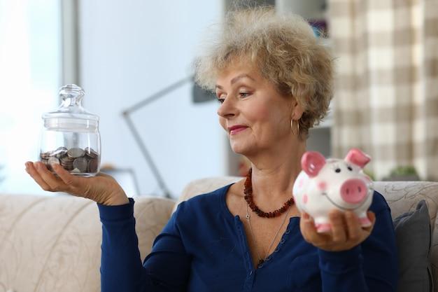 Mulher segura cofrinho com economias nas mãos dela.