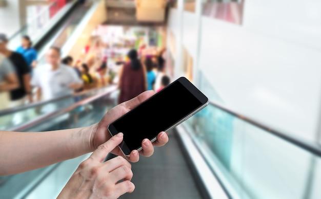 Mulher segura com a mão e tela sensível ao toque em um smartphone na escada rolante turva com pessoas