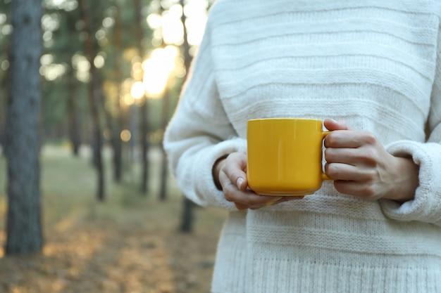 Mulher segura copo amarelo na floresta, espaço para texto